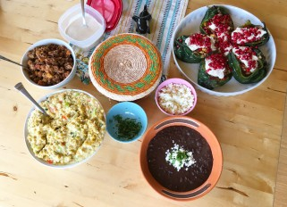 Chiles en nogada, Mexican dish ( stuffed poblano with meat, fruits, spices and walnut sauce ), black beans and Picadillo de platano verde, Costa Rican dish; also homemade corn tortilla.